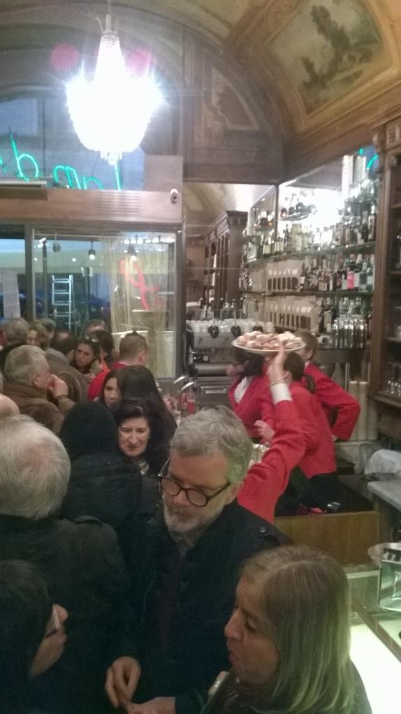 La folla all'interno del bar e i camerieri in giacca rossa
